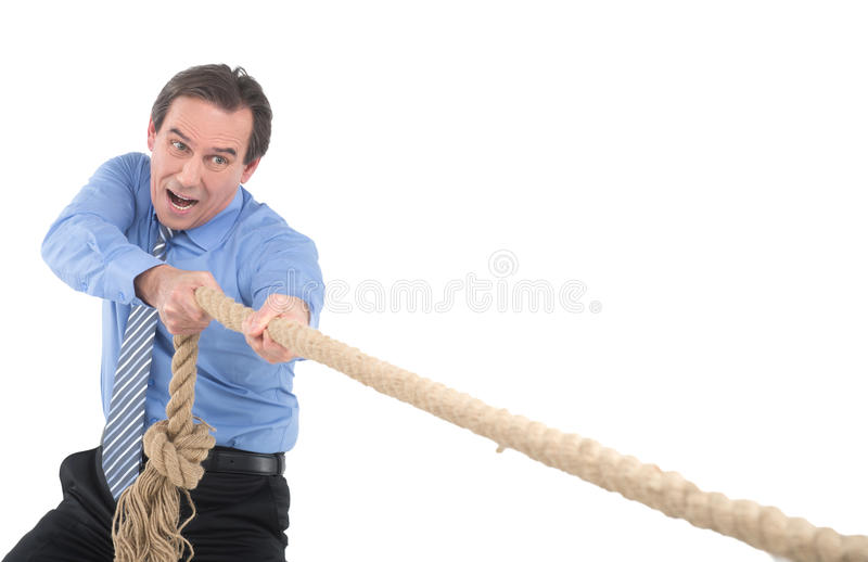 Business competition. Confident mature businessman pulling a rope while standing isolated on white stock photos
