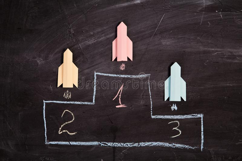 Business competition, rivalry, challenge or dispute. Success and strategy concept. Paper rockets on prize places.  royalty free stock photo