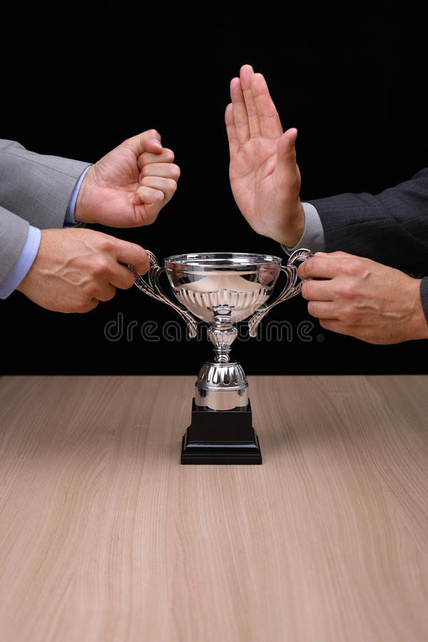 Business competition. Business rivalry and confrontation at work, two businessmen fighting over a silver trophy stock image