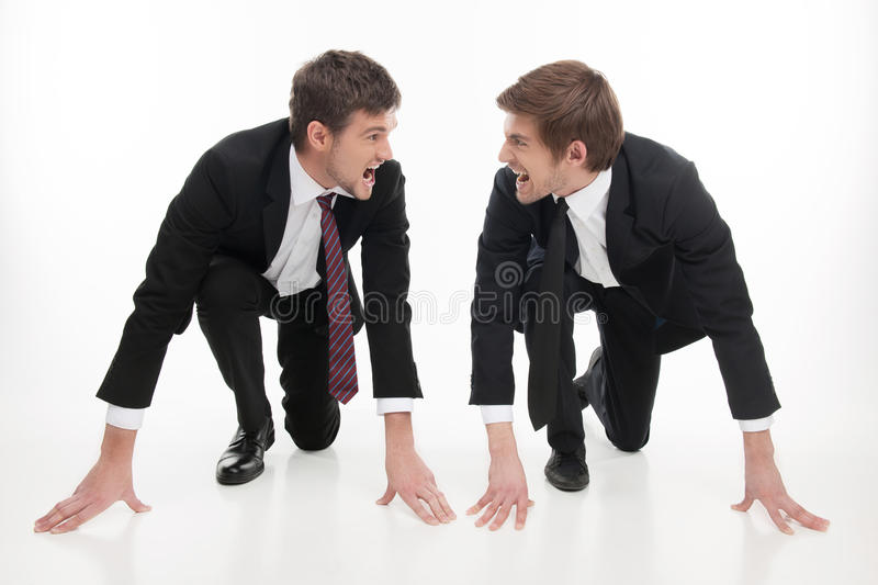 Business competition. Two angry young business people standing at the start line and looking at each other while isolated on white royalty free stock photo