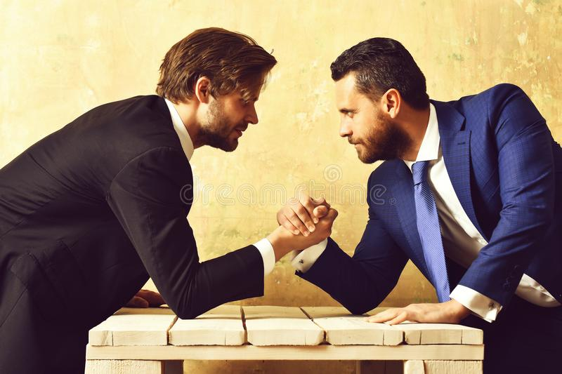 Business competition. Two serious businessmen arm wrestling. In suit stock photo