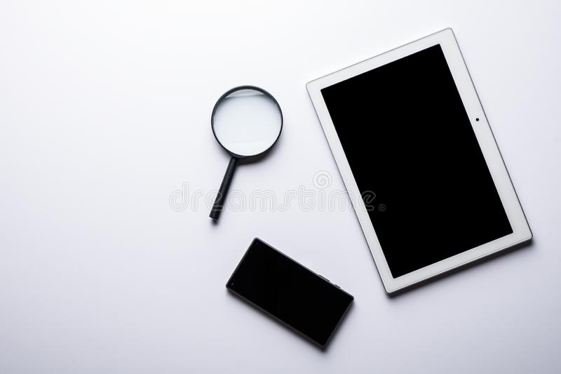 Business composition from tablet, smartphone and magnifier. Net search. business composition from tablet, smartphone and magnifier royalty free stock photo