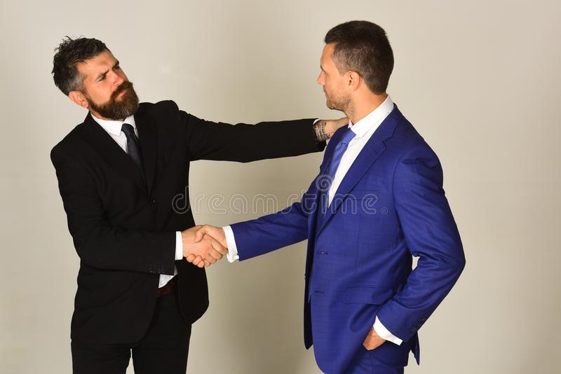 Business and compromise concept. Executives shake hands in agreement. On light grey background. Businessmen wear smart suits and ties. Men with beard and stock image
