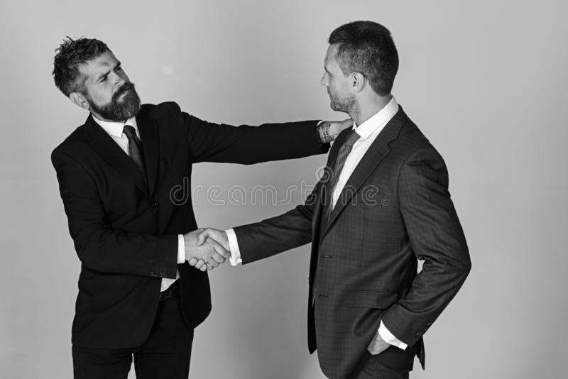 Business and compromise concept. Executives shake hands in agreement. On light grey background. Businessmen wear smart suits and ties. Men with beard and stock images