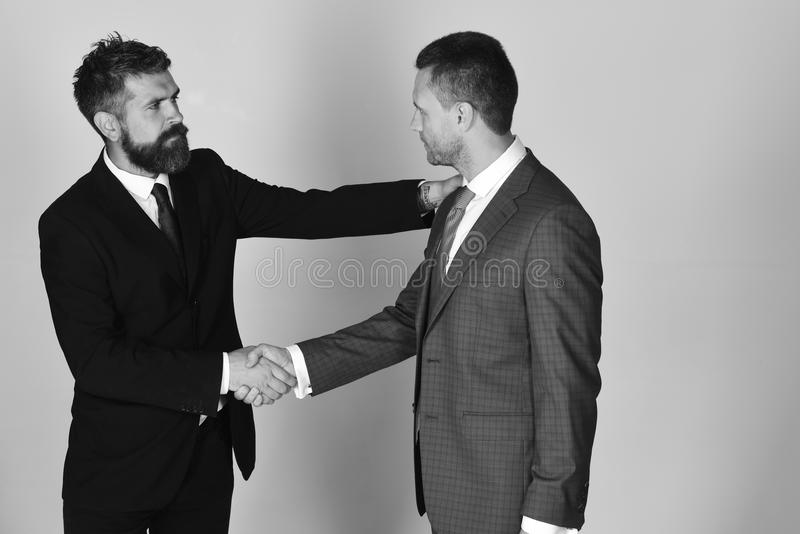 Business and compromise concept. Executives shake hands in agreement on light grey background. Businessmen wear smart suits and ties. Men with beard and royalty free stock photo