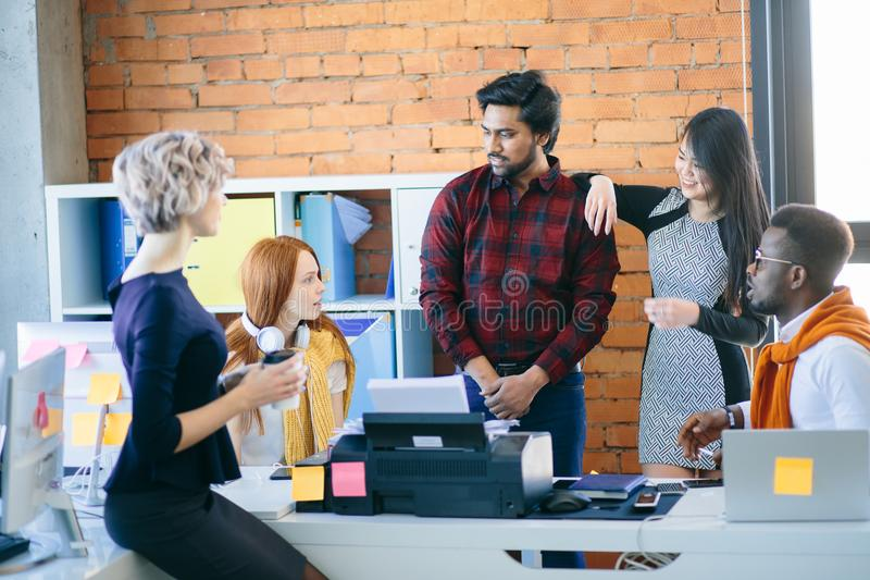 Conversation among mixed race office workers in casual clothes. Business comunication. conversation among mixed race office workers in casual clothes in the royalty free stock photography