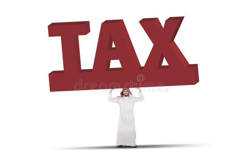 Arabian businessman lifting a big and heavy word of Tax isolated over white. Business concept: Arabian businessman lifting a big and heavy word of Tax isolated stock photography
