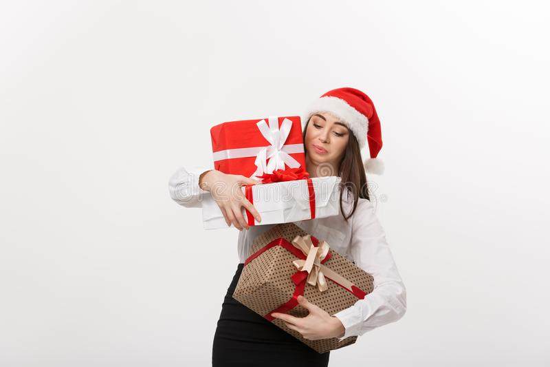 Business Concept - Beautiful young caucasian business woman with santa hat holding too much christmas gift boxes with. Worry face royalty free stock photo