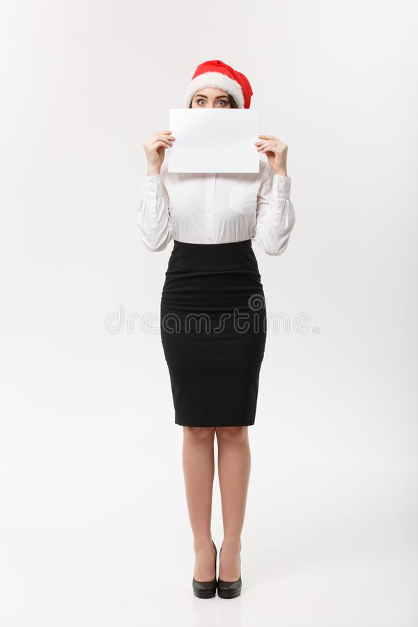 Business Concept - Beautiful young confident business woman with santa hat hiding behide white blank paper with. Surprising facial expression royalty free stock photos