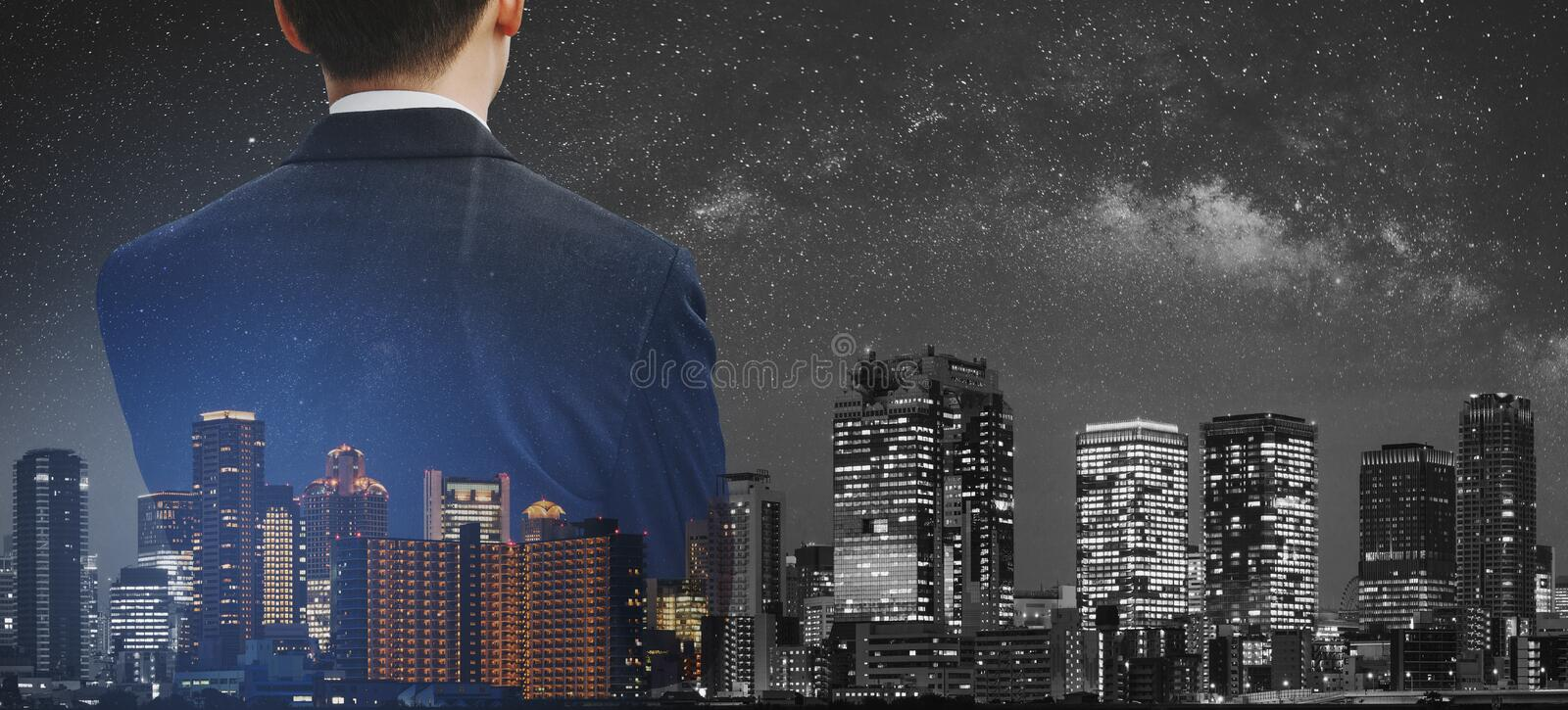Business concept, Businessman in black suit with double exposure panoramic modern city at night stock images
