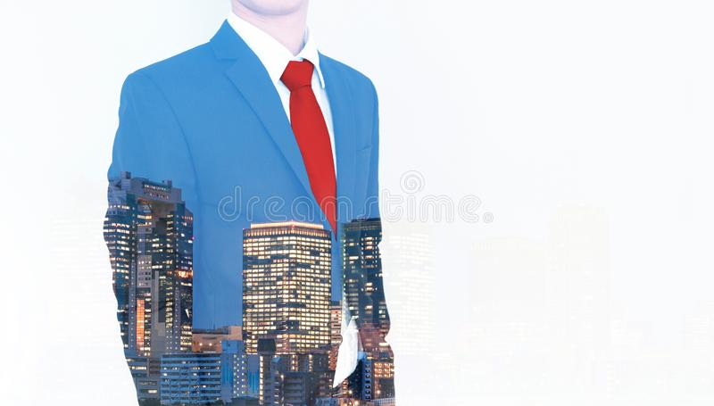 Business concept. Businessman in blue suit and red necktie, with double exposure panoramic business office buildings in the city royalty free stock image