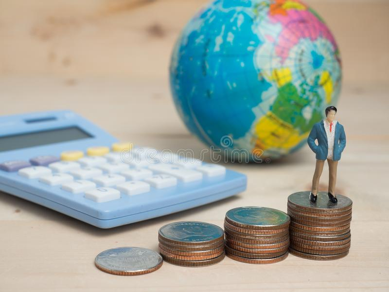 Business Concept. businessman small figures standing on calcula. Tor.Money and Business Concept. Businessman small figure standing stock photography