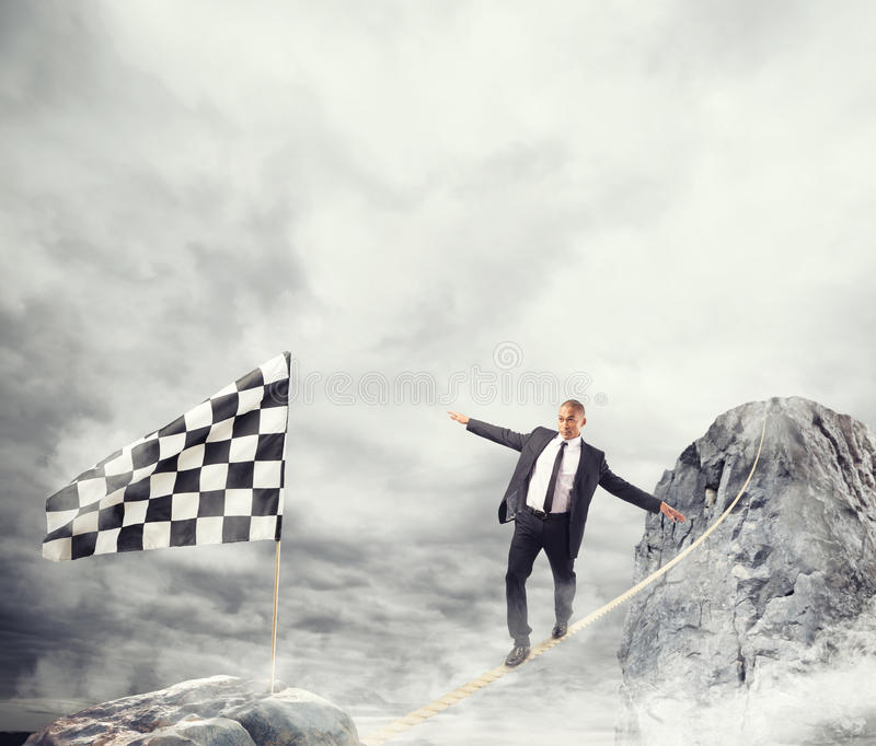 Business concept of businessman who overcome the problems reaching the flag on a rope. Business concept of businessman who overcome the problems reaching the stock photography