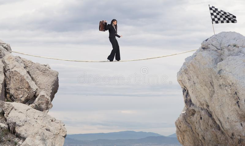 Business concept of businesswoman who overcome the problems reaching the flag on a rope stock image
