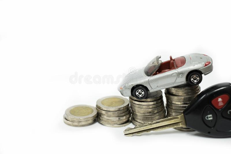 Business concept of car loan, gray car and stacks of coins. Money management for car concept, finance concept trade car for cash, on white background stock photography