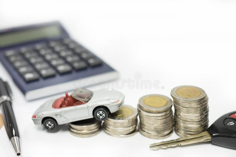 Business concept of car loan, gray car and stacks of coins. Money management for car concept, finance concept trade car for cash, isolated on white background stock image
