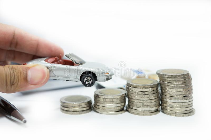 Business concept of car loan, gray car and stacks of coins. Money management for car concept, finance concept trade car for cash, isolated on white background stock images
