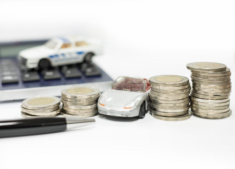 Business concept of car loan, gray car and stacks of coins. Money management for car concept, finance concept trade car for cash, isolated on white background royalty free stock photography