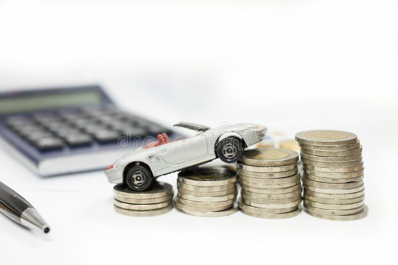 Business concept of car loan, gray car and stacks of coins. Money management for car concept, finance concept trade car for cash, isolated on white background royalty free stock image
