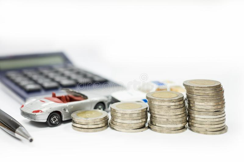 Business concept of car loan, gray car and stacks of coins. Money management for car concept, finance concept trade car for cash, isolated on white background royalty free stock photos