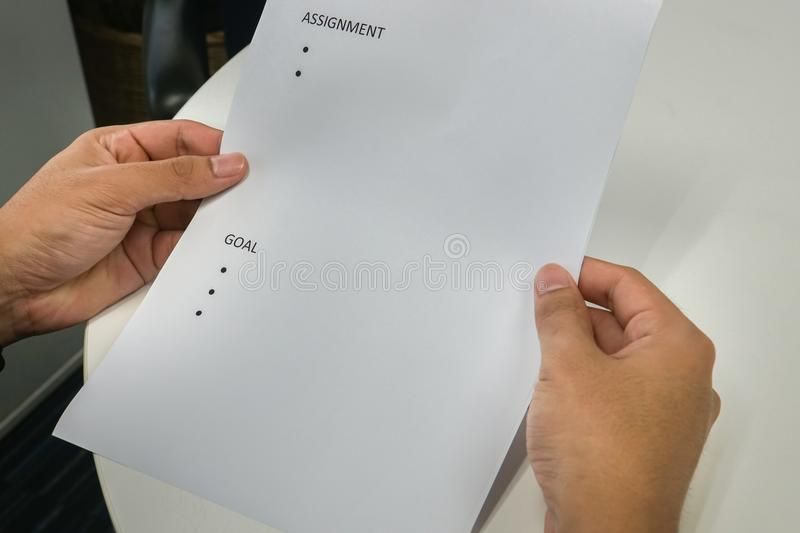 Close up employee hold mock up paper of assignment and goals for performance review stock images
