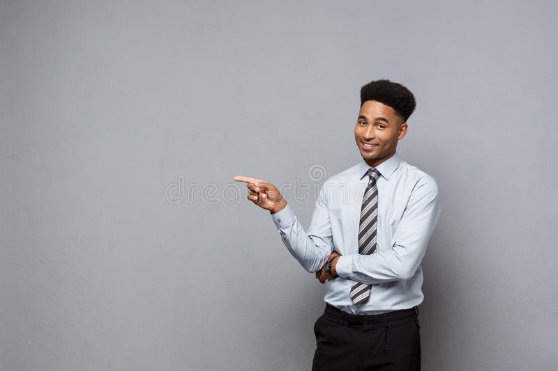 Business Concept - Confident thoughtful young African American pointing finger on side over grey background. Business Concept - Confident thoughtful young stock photo
