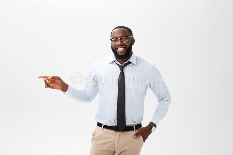 Business Concept - Confident thoughtful young African American pointing finger on side over grey background. Business Concept - Confident thoughtful young royalty free stock images