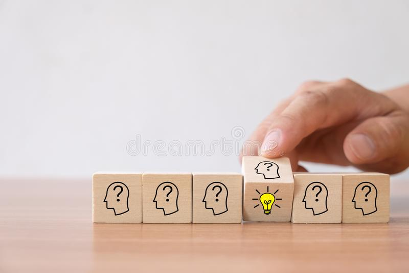 Business concept of creative idea and innovation. Hand flip over wooden cube block with light bulb icon new idea and head human symbol have no idea stock photography