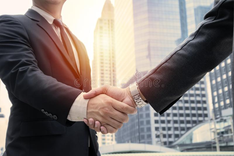 Business concept. deal, joint venture, start up. Businessmen handshaking, on city building background, employment and hiring, enterprisers making good business stock images
