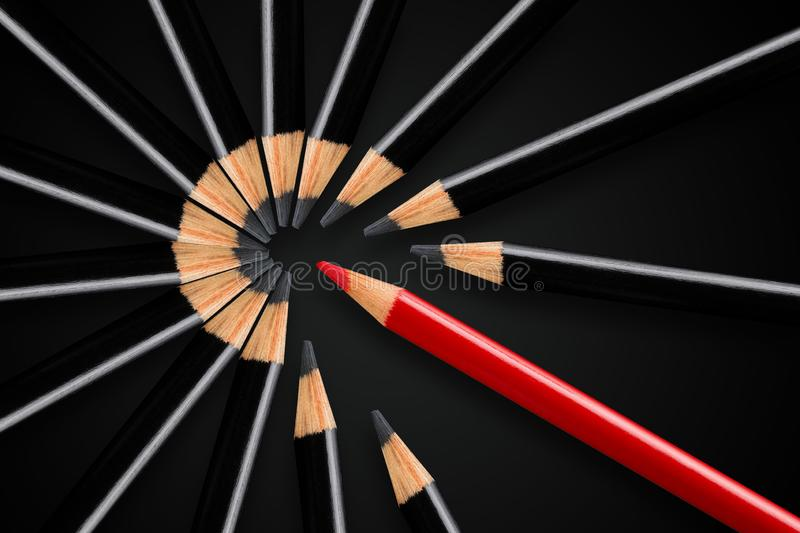 Business concept of disruption, leadership or think different; red pencil breaking apart circle of black pencils. Business concept of disruption, leadership or stock photos