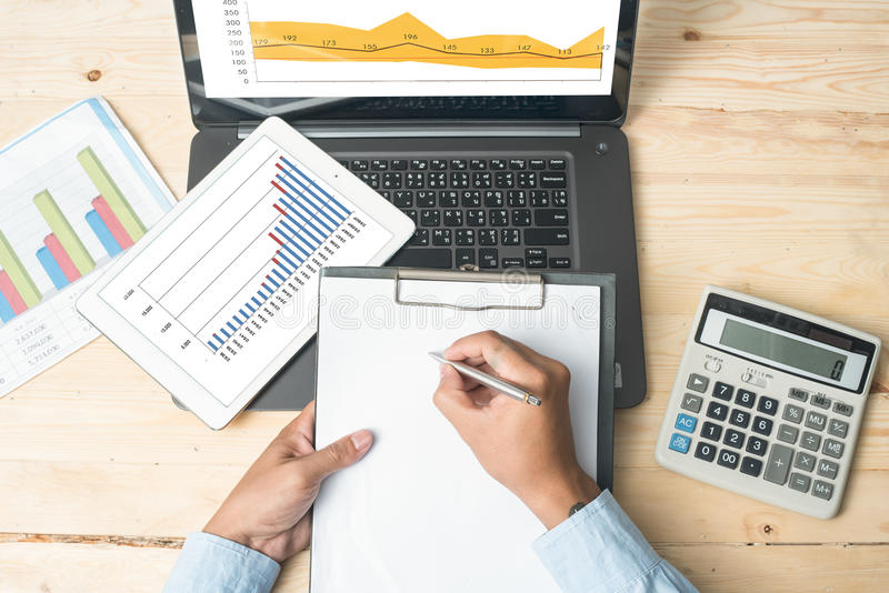Business concept - graph, calculator, tablet and pen on desk royalty free stock image