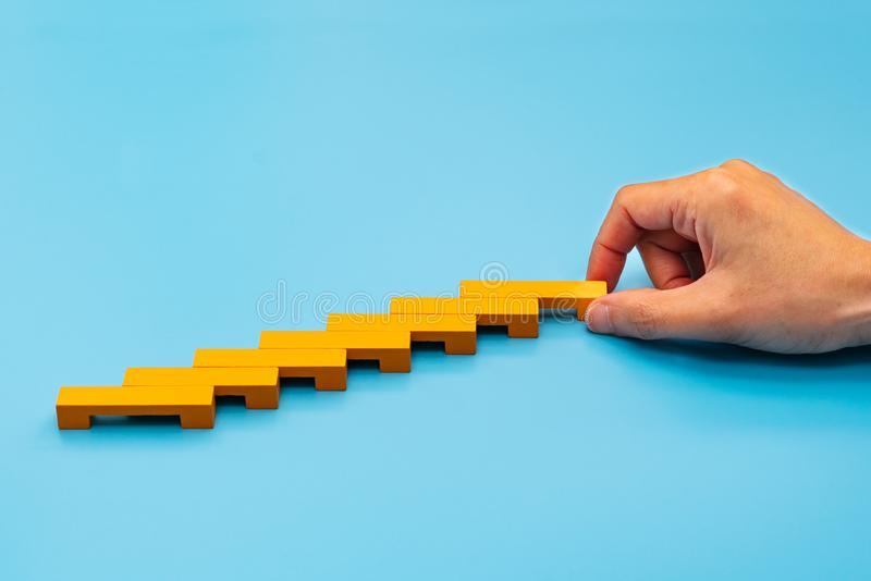 Business concept for growth success process, hand stacking wood block as step stair stock photography