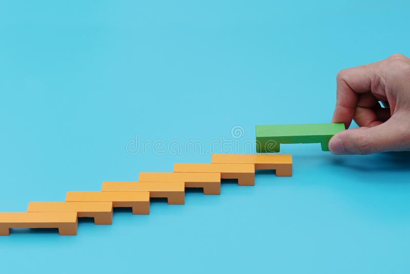 Business concept for growth success process, hand stacking wood block as step stair royalty free stock image