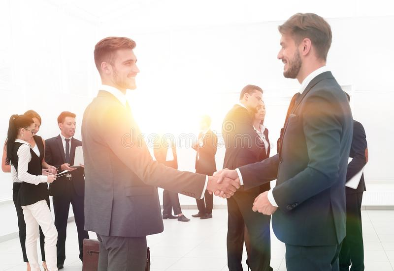 Handshake of business partners on the background of business tea. Business concept.handshake of business partners on the background of business team stock photography