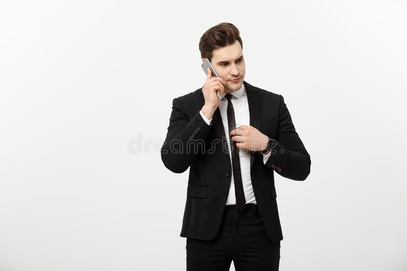 Business Concept: Handsome businessman in suit and speaking on the phone over isolated grey background. stock photos