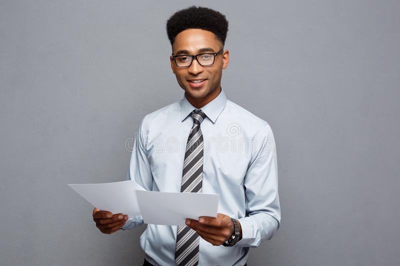 Business Concept - handsome young professional african american businessman holding report papers. stock photography