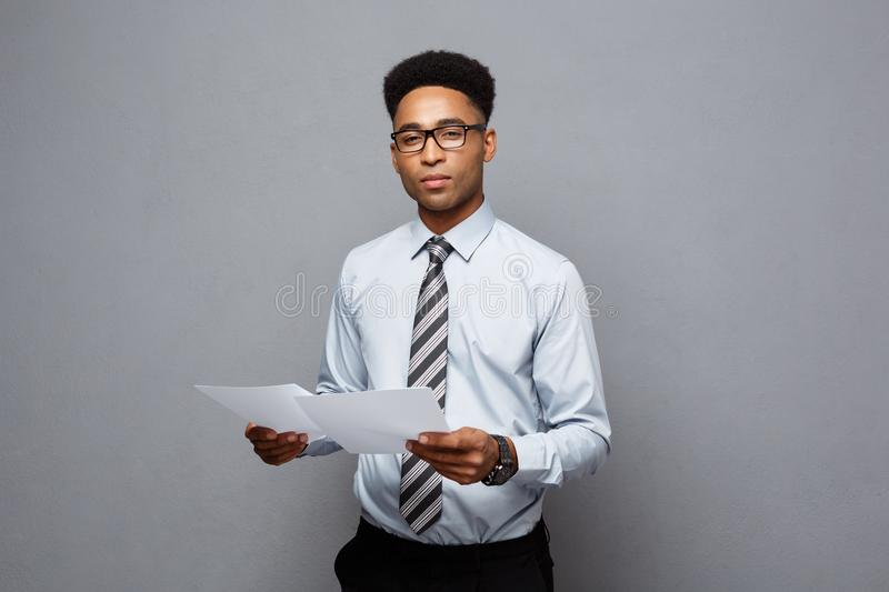 Business Concept - handsome young professional african american businessman holding report papers. stock photos
