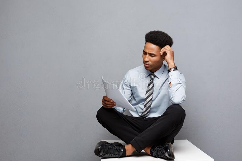 Business Concept - handsome young professional african american businessman serious reading paperworks. stock photos