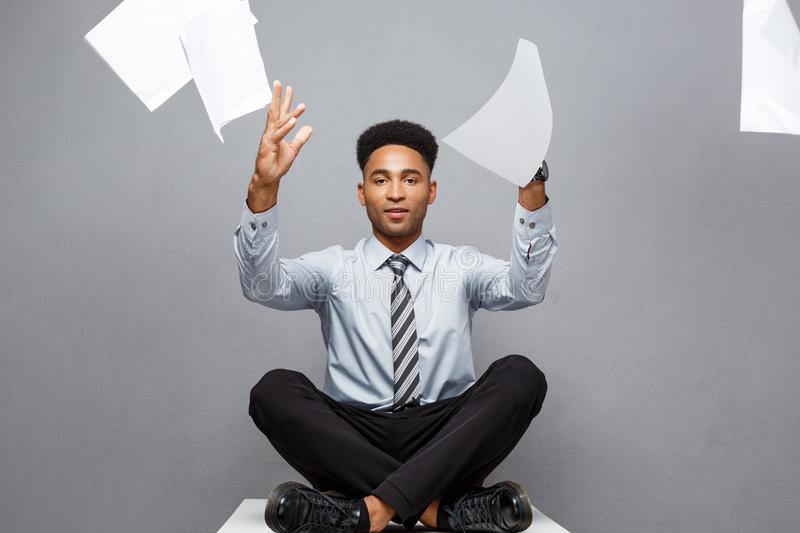 Business Concept - handsome young professional african american businessman throwing away pile of paperworks flying on stock photos