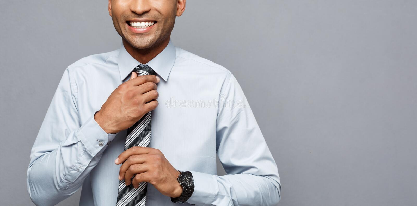 Business Concept - Happy confident professional african american businessman posing over grey background. royalty free stock photo