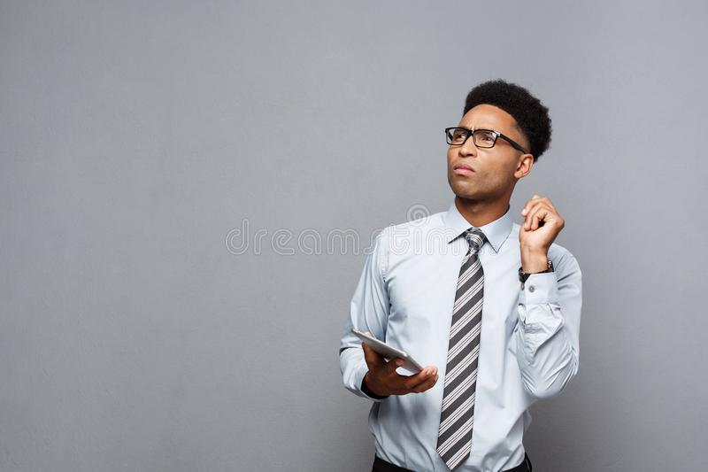 Business Concept - Happy handsome professional african american businessman shocking and thinking with digital tablet on royalty free stock photos
