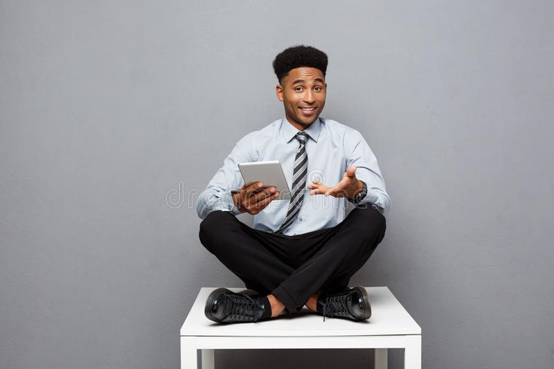 Business Concept - Happy handsome professional african american businessman texting on digital tablet to client. stock photo