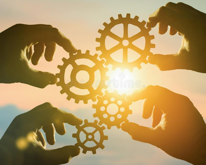 Business concept idea. four hands of businessmen collect a puzzle from gears. Cooperation, teamwork, strategy, creativity, innovation royalty free stock image