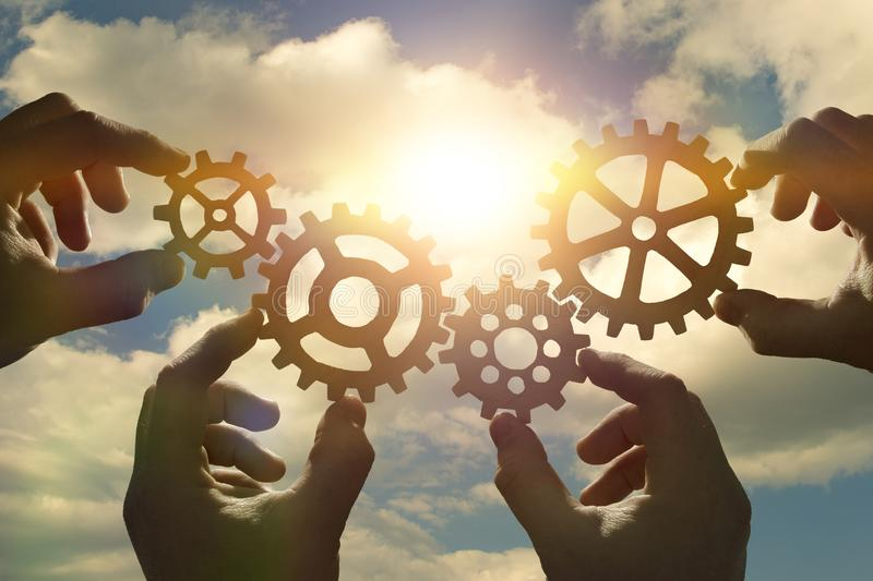 Business concept idea. four hands of businessmen collect a puzzle from gears. Cooperation, teamwork, strategy, creativity, innovation stock images