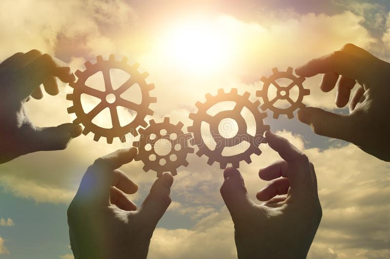 Business concept idea. four hands of businessmen collect a puzzle from gears. Cooperation, teamwork, strategy, creativity, innovation stock photo