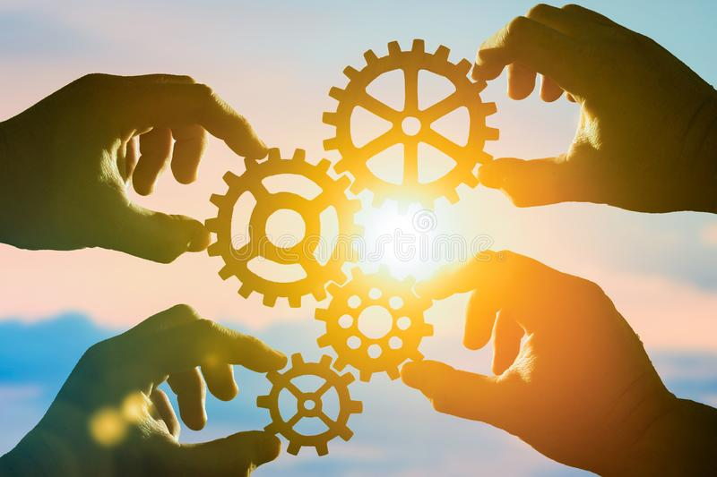 Business concept idea. four hands of businessmen collect a puzzle from gears. Cooperation, teamwork, strategy, creativity, innovation royalty free stock photography