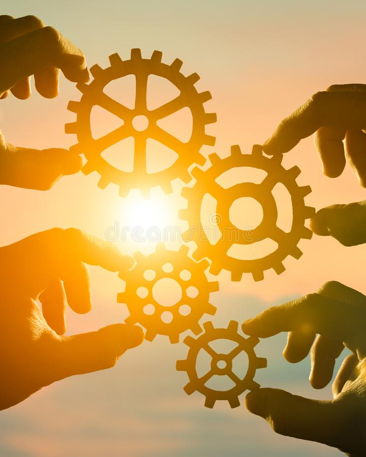 Business concept idea. four hands of businessmen collect a puzzle from gears. Cooperation, teamwork, strategy, creativity, innovation stock image
