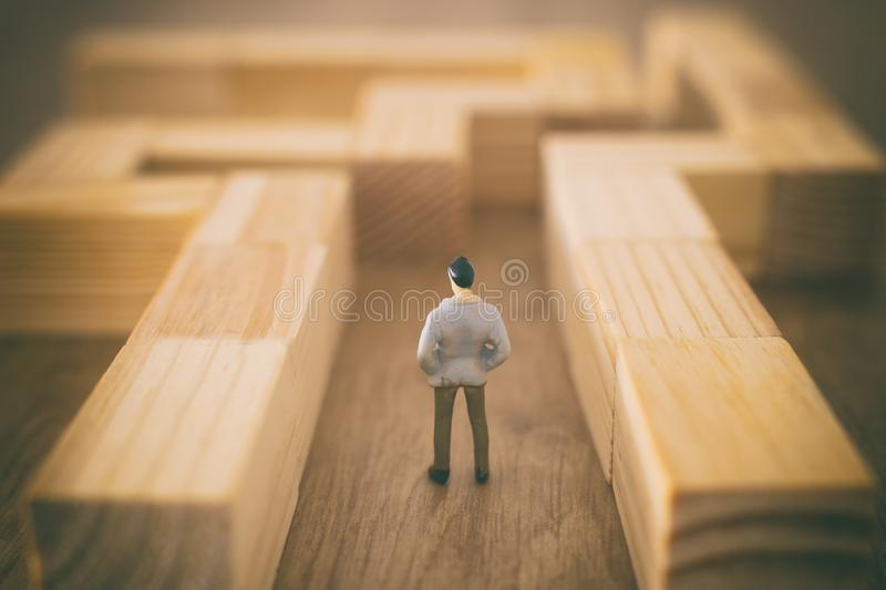 Business concept image of and challenge. A man stands in the maze looking for the exit. Problem solving and decision making idea stock images