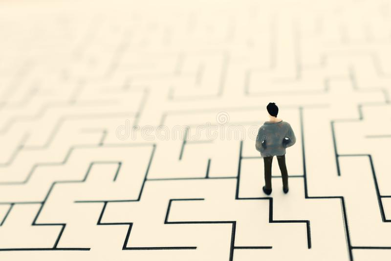 Business concept image of and challenge. A man stands in the maze looking for the exit. Problem solving and decision making idea.  royalty free stock photo