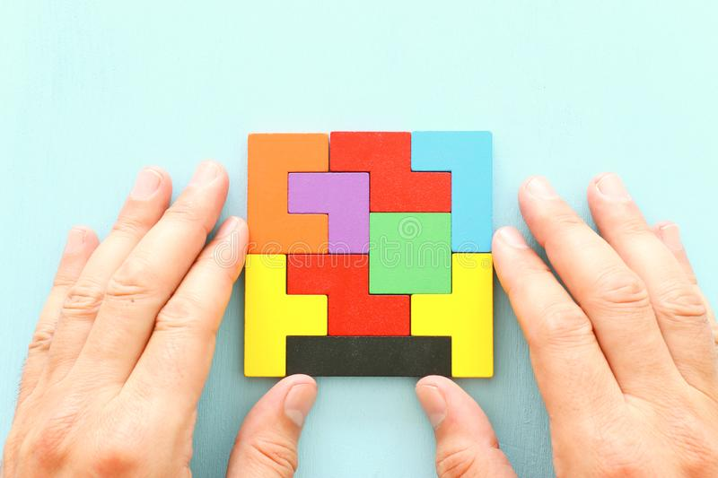 Business concept image of a colorful square tangram puzzle, over wooden table royalty free stock image
